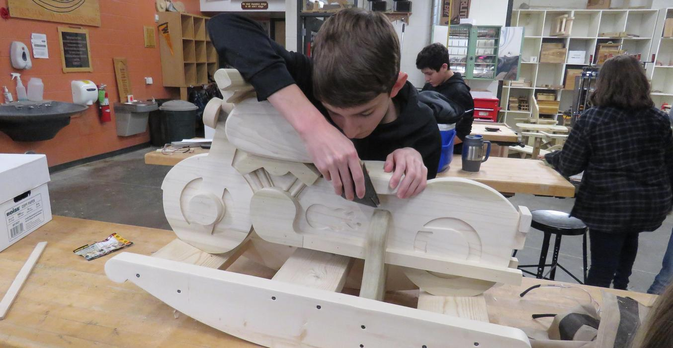 Woods students spend hours sanding the wooden rocking toys given away at Christmas.