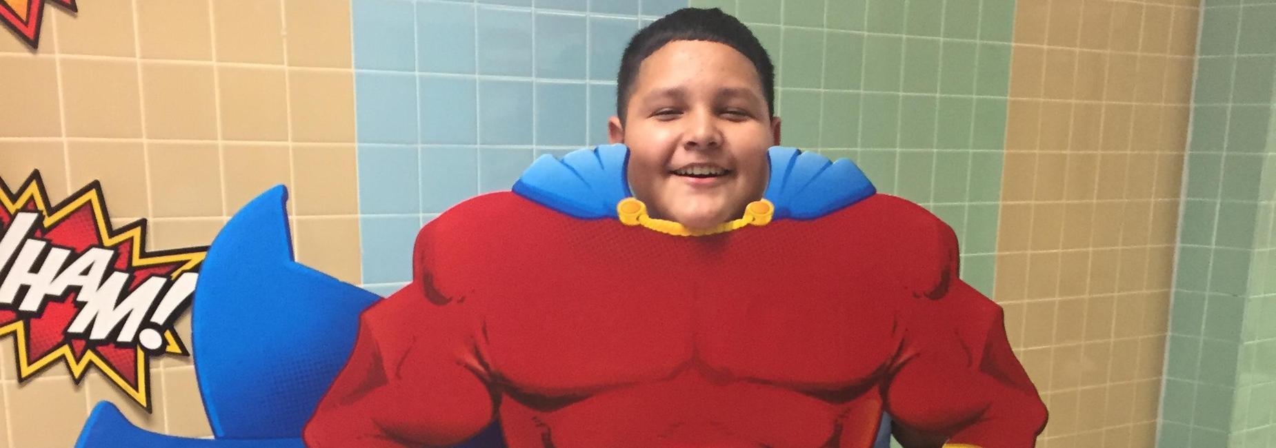 Student posing with superhero cutout .  Estudiante posando con recorte de superhéroe