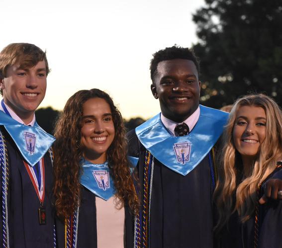4 students in graduation regalia hugging and smiling