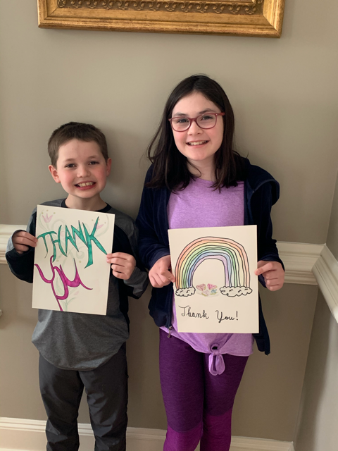 image of boy and girl holding thank you drawings