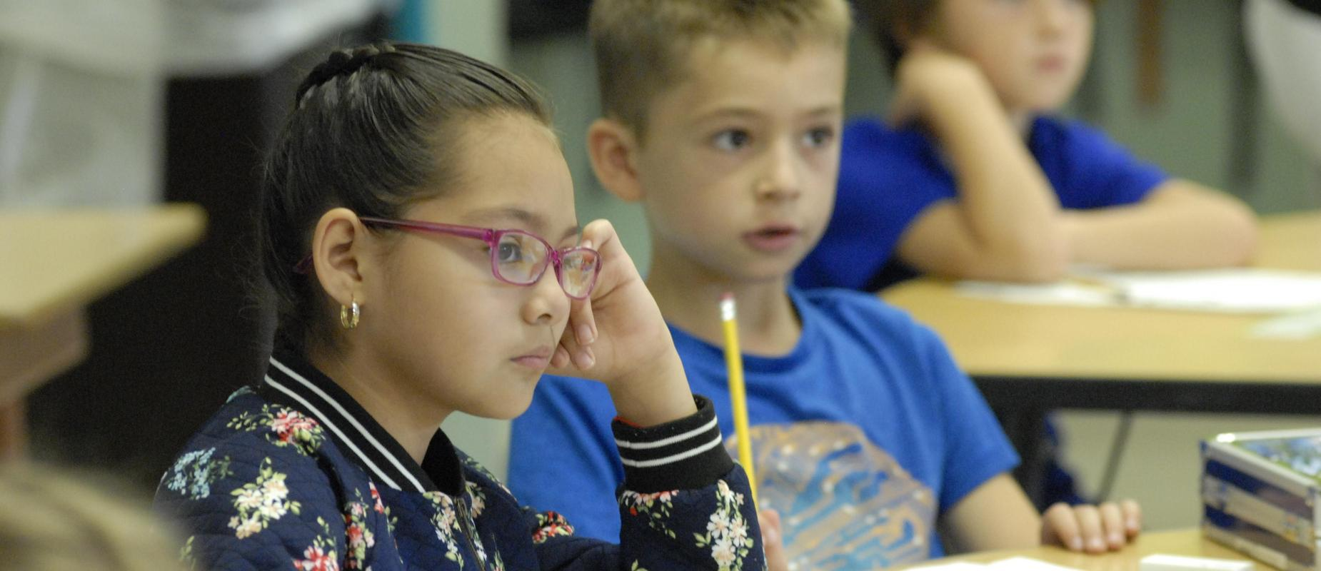 Little children listening to teacher in classroom