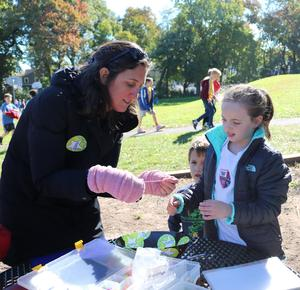 Parent Debi Kapuscinski (left) helps 4th grader Scarlett Goldman prepare a charm necklace to which the student will add as she completes additional laps in the Recess Runners' Club at Washington School.