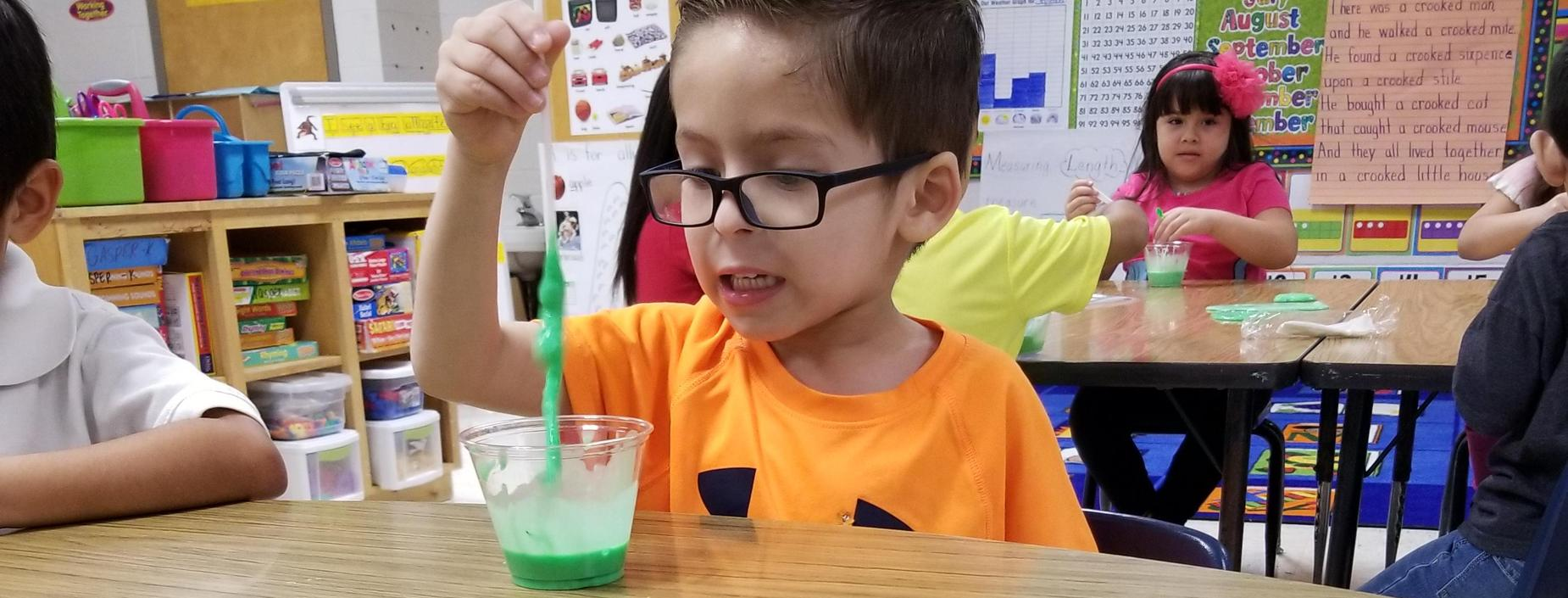 A kindergarten students plays with his green slime creation.