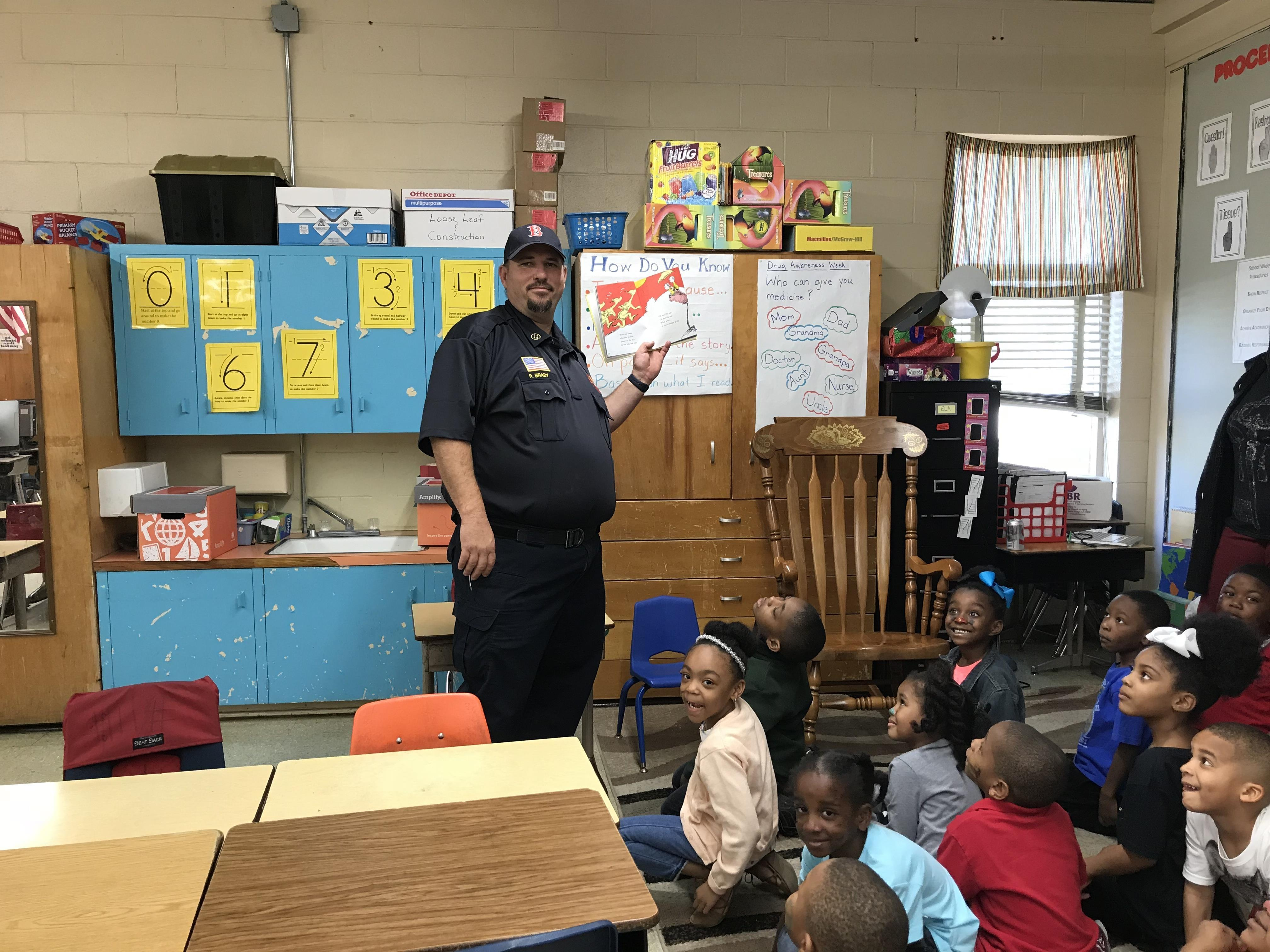 a photo of one member of the Baker Fire Department reading to a classroom of students at Park Ridge Academic Magnet School