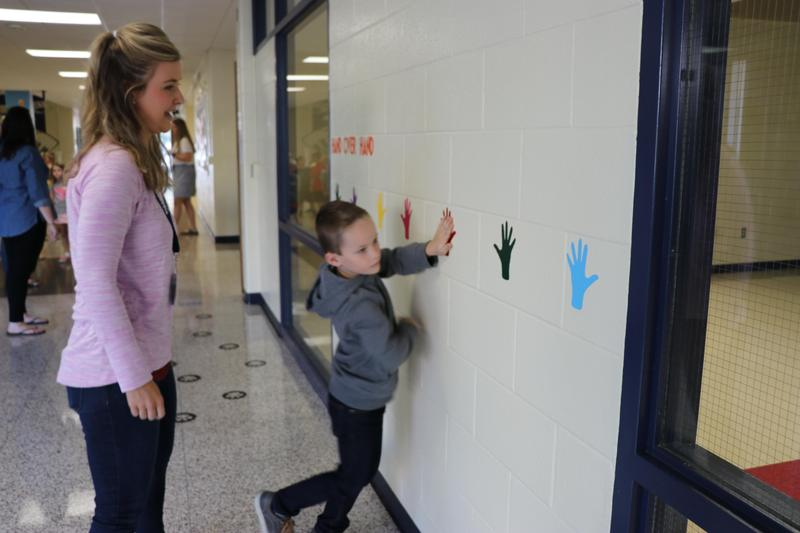Ms. Busch stands next to a student at the hand over hand activity