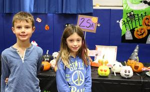 Two 2nd graders pose in front of pumpkin decoration/carvings created for the Wilson Pumpkin Patch.
