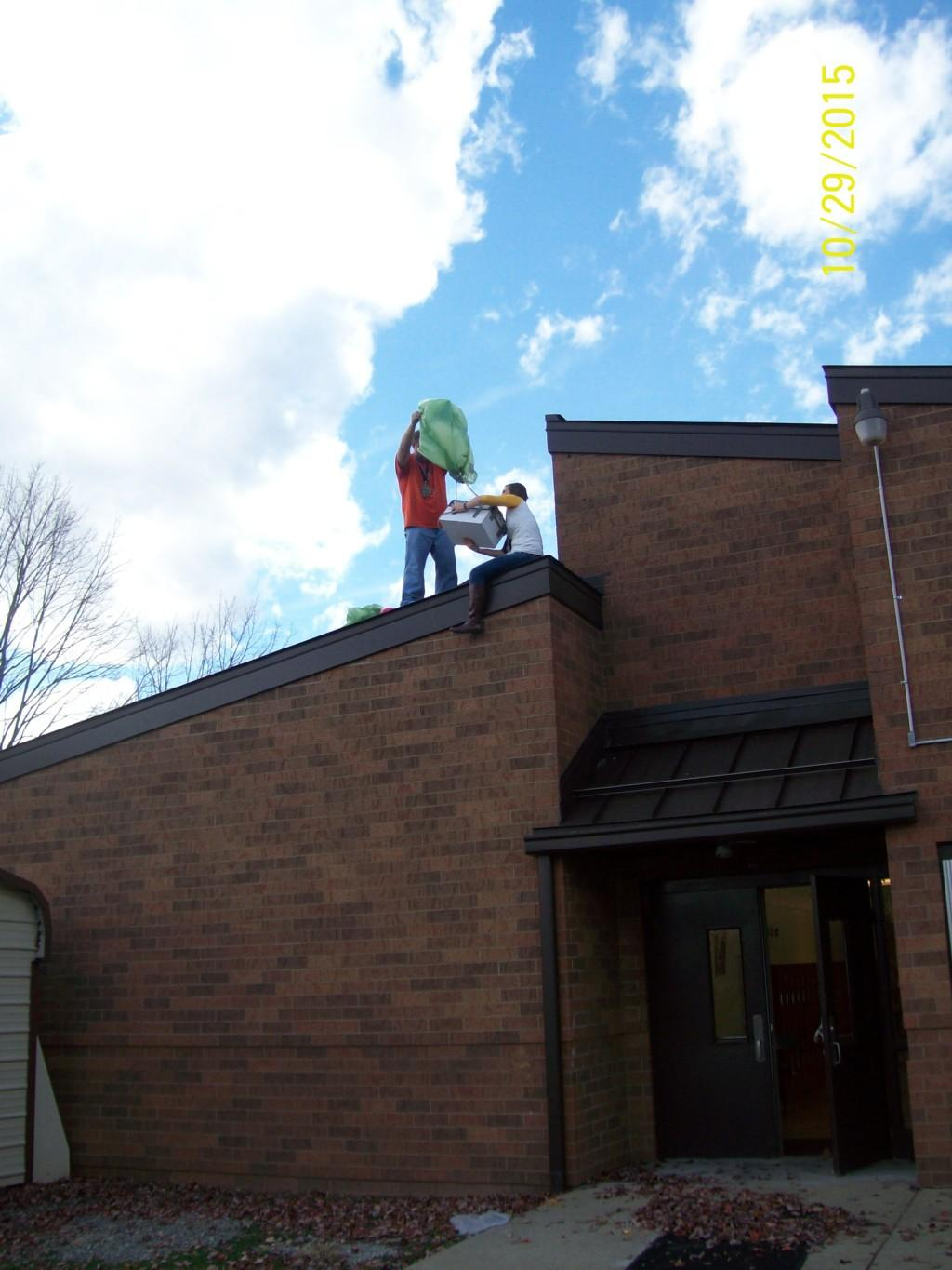 Mr. Kelley and Ms. Mason on the roof preparing for the pumpkin drop