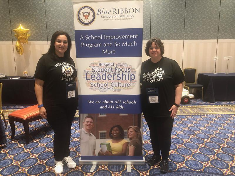 Mrs. Rojas and Mrs. Perez in front of the Schools of Excellence Blue Ribbon Schools Banner