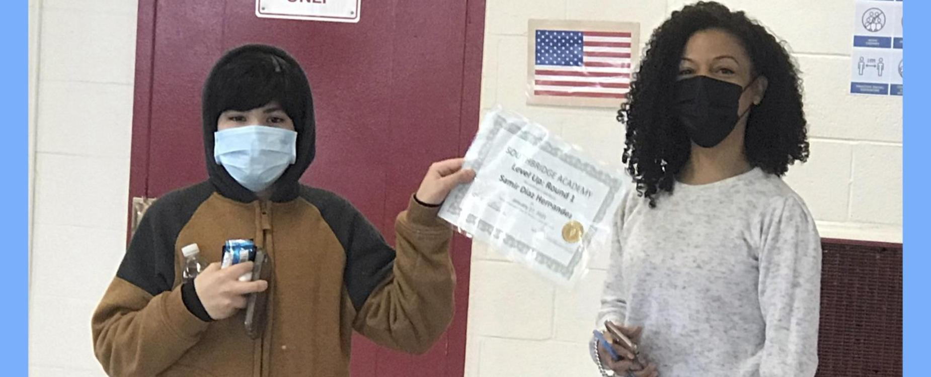 Photo of a student at Southbridge Academy receiving a certificate of recognition from a staff member