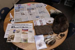 Several newspapers and souvenirs set out on a table.
