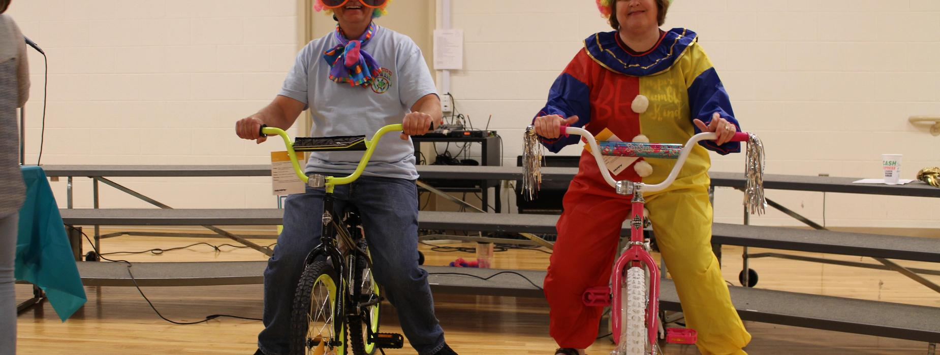 Picture of Principal Robert Hooper and Assistant Principal Laura Jones dressed as clowns sitting on AR bikes.
