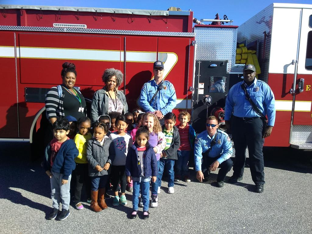 Students pose with firemen and firetruck.