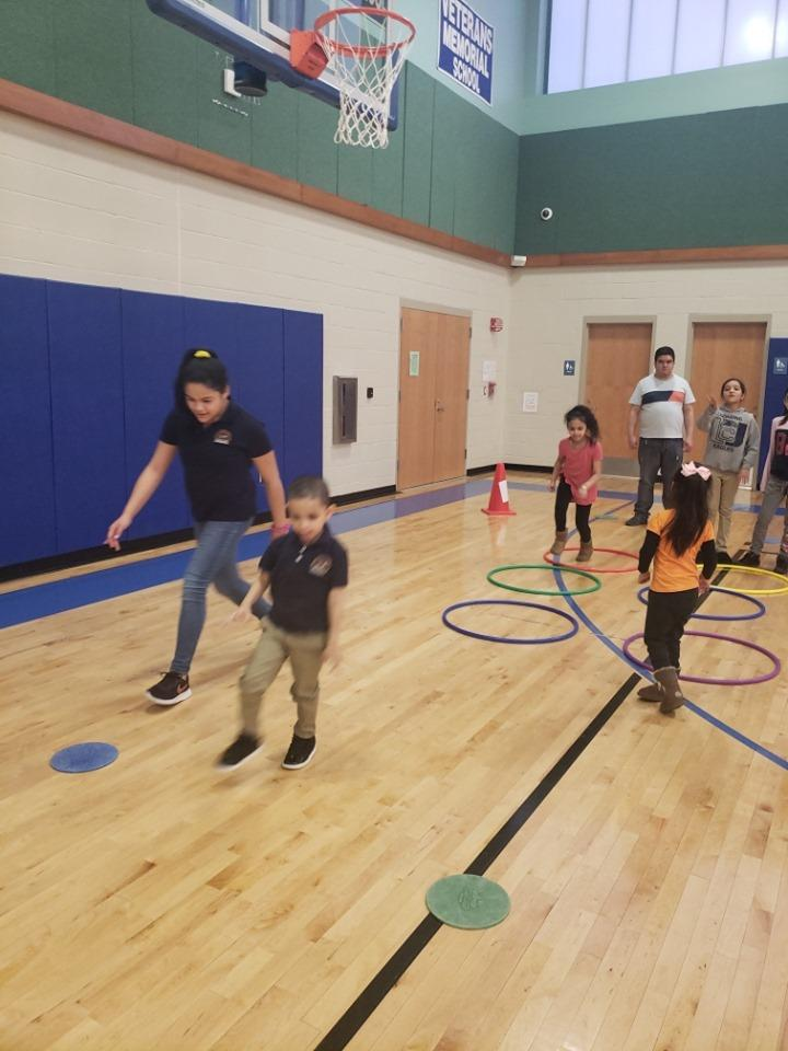 Little kids with older kids jumping into hoola hoop circles as part of a course