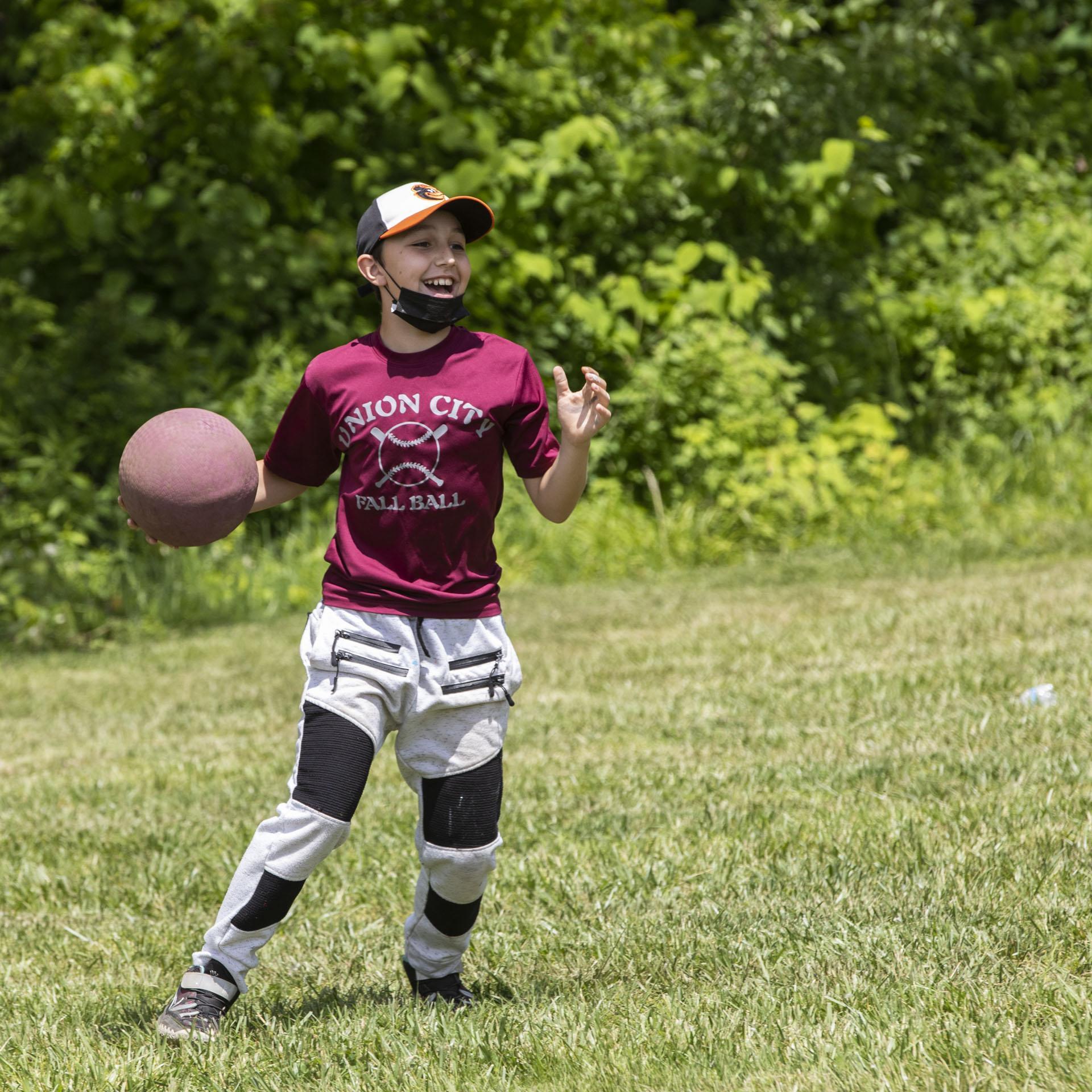 Boy holding kick ball