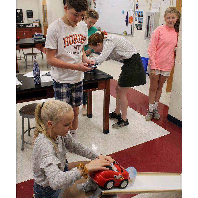 Students collaborate on a science experiment dealing with force and motion.