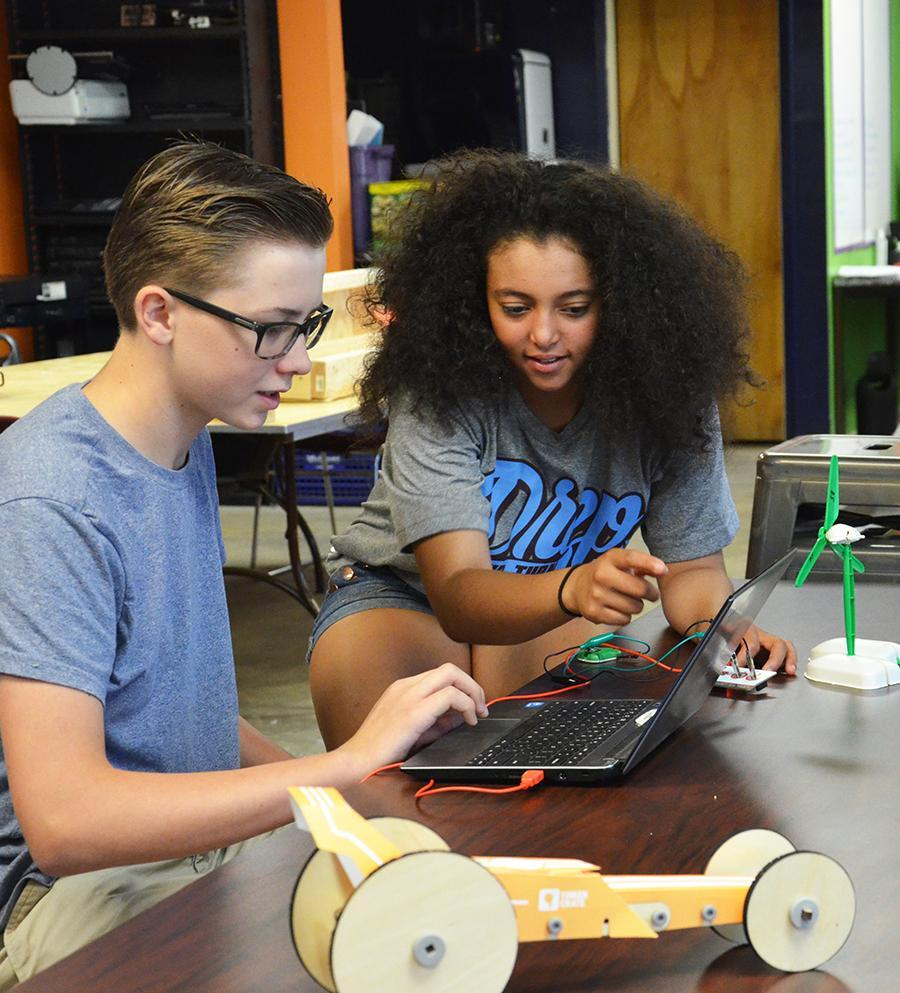 Upper school students work on a laptop to make model windmill work