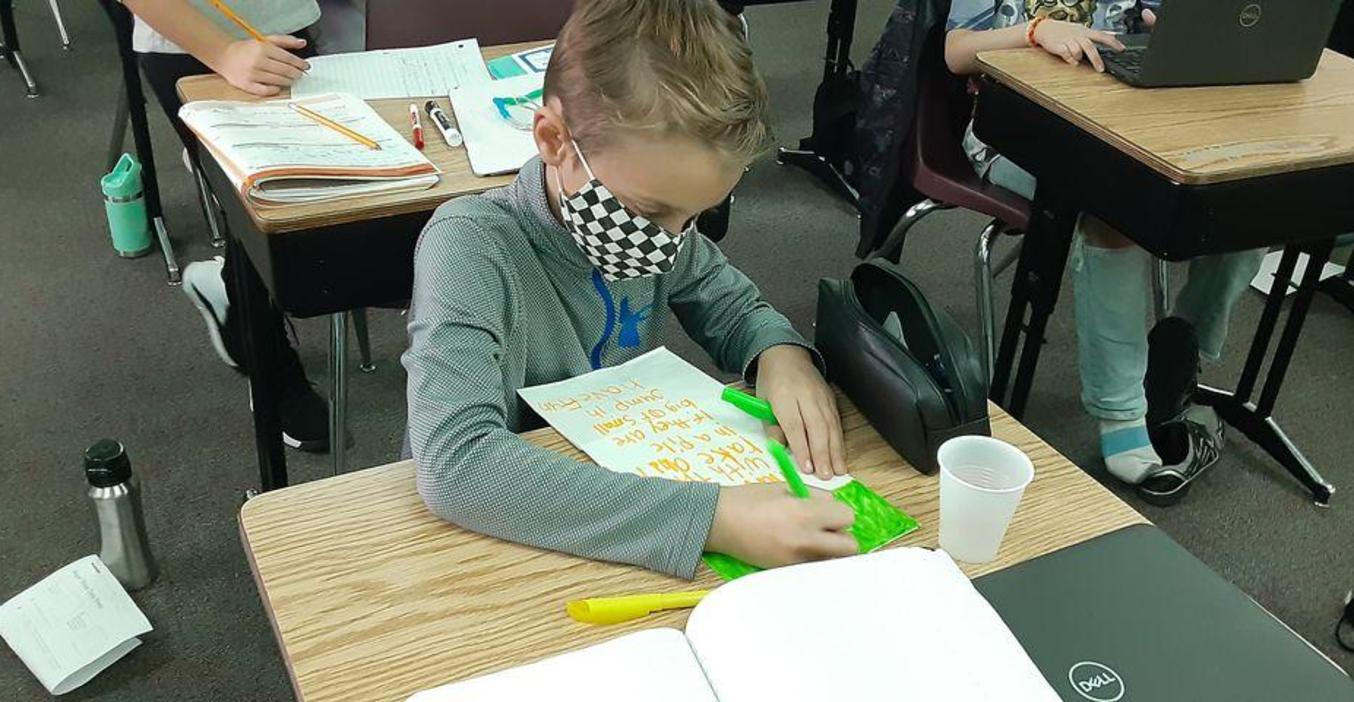 A Page student works on decorating a plain paper bag for Kids Food Basket.