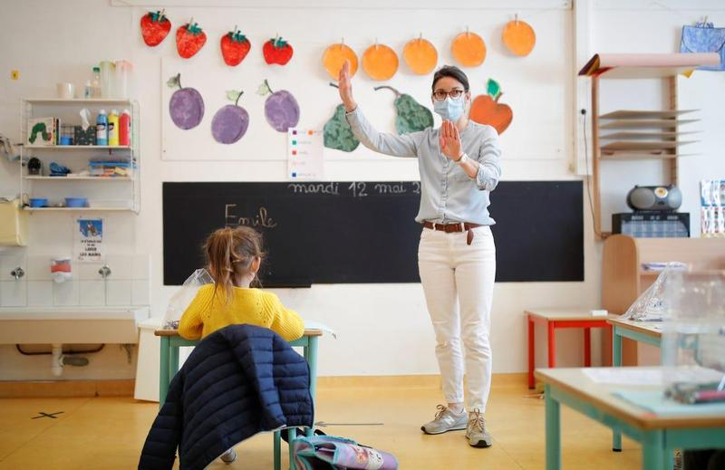Teacher wearing face mask in front of student in classroom