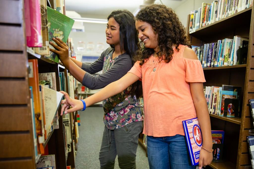 Students picking books from shelves