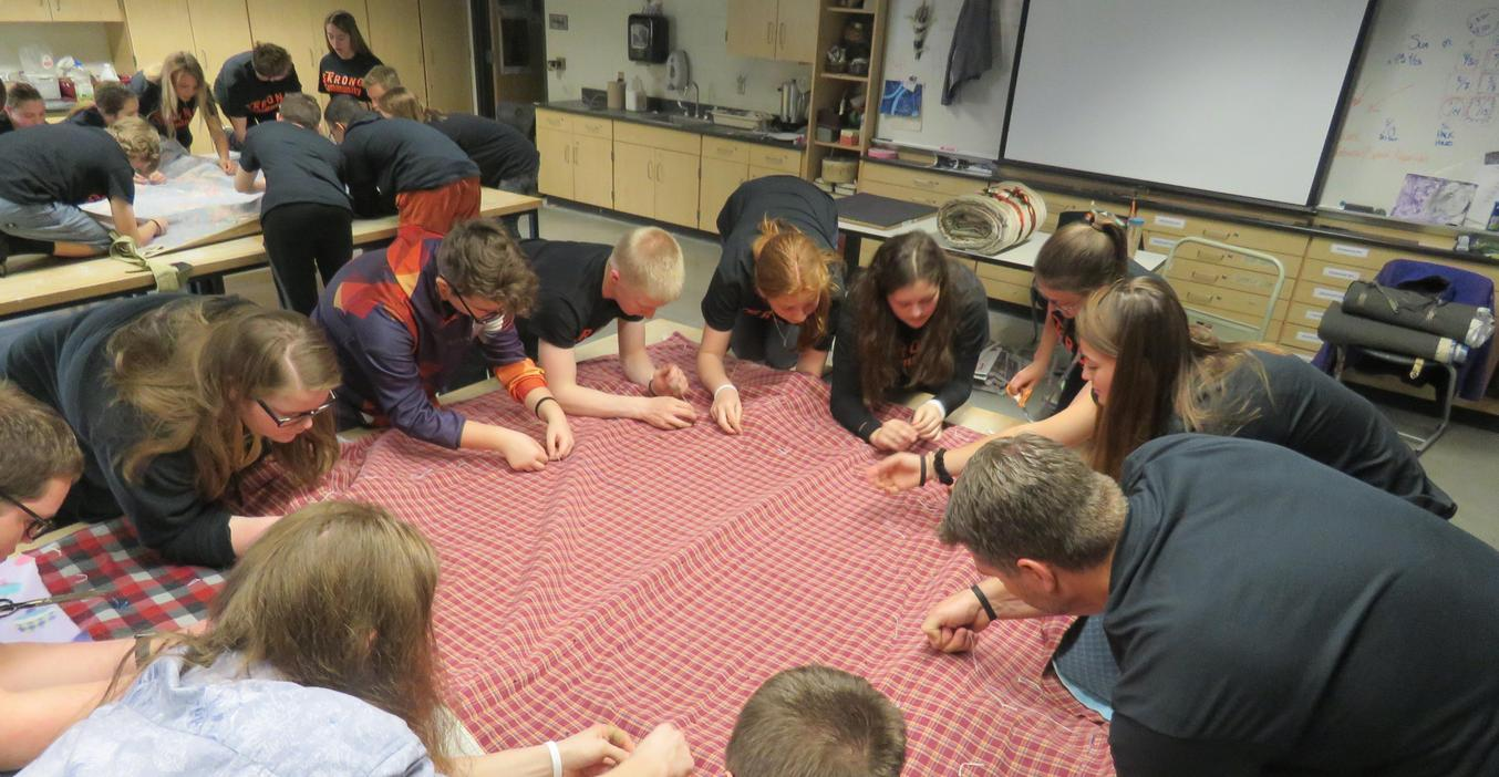 TKHS students sew blankets together to make sleeping bags for the homeless as part of their service day projects.