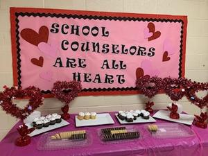 A table displays cupcakes and valentine's decor