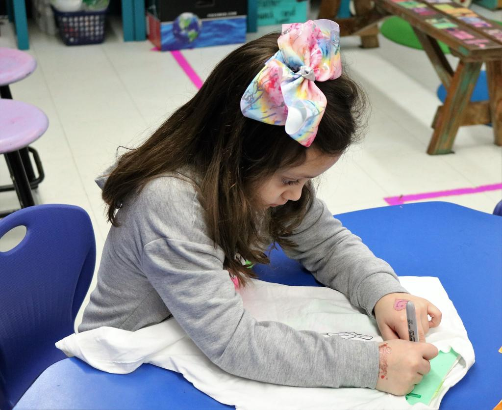 Photo of Tamaques 1st grader working on t-shirt for 100th Day activities.