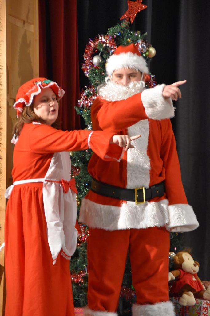 Santa Claus and Mrs. Claus point to the audience
