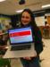 Yael displaying email award from laptop