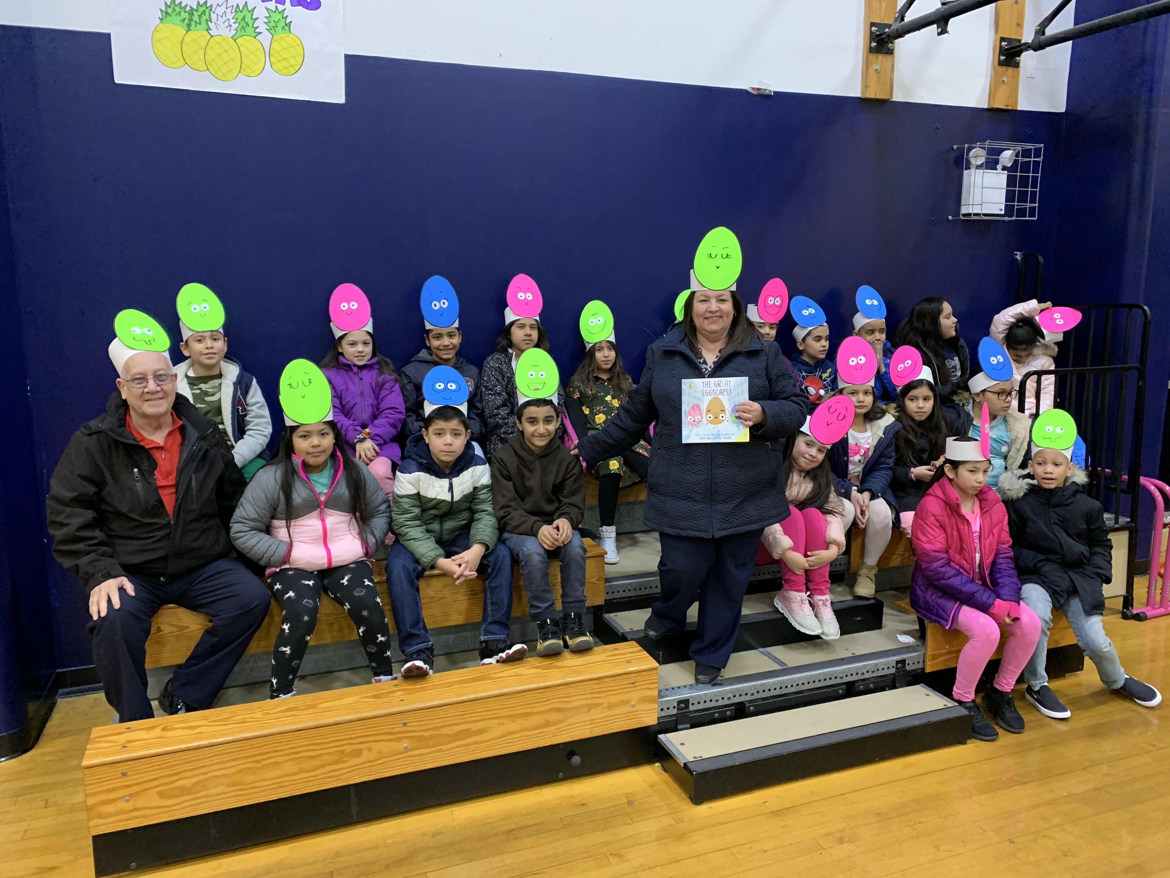 teacher with class wearing large egg hats like their book the great egg escqape