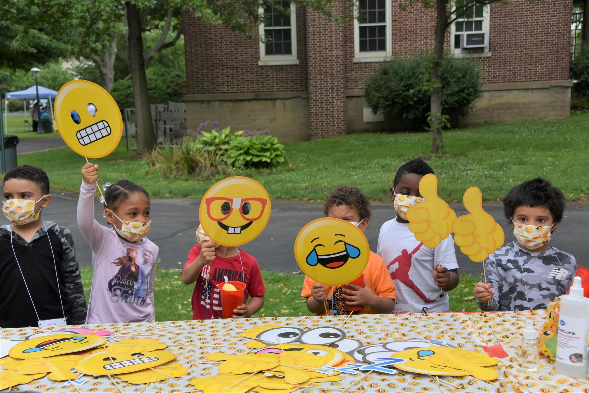 A class is holding up emoji signs at a photobooth table