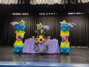 stage display for the awards ceremony decorated with balloons, flowers, etc.