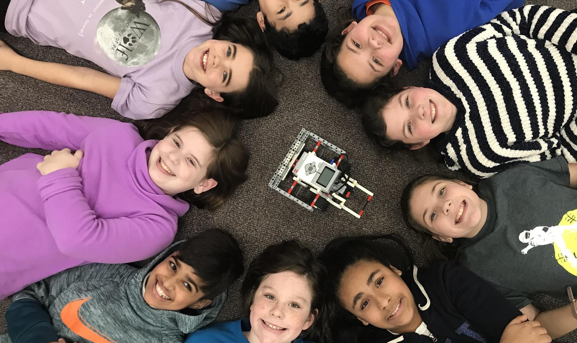 9 smiling students laying in a circle with their face up, surrounding a robot that they coded.