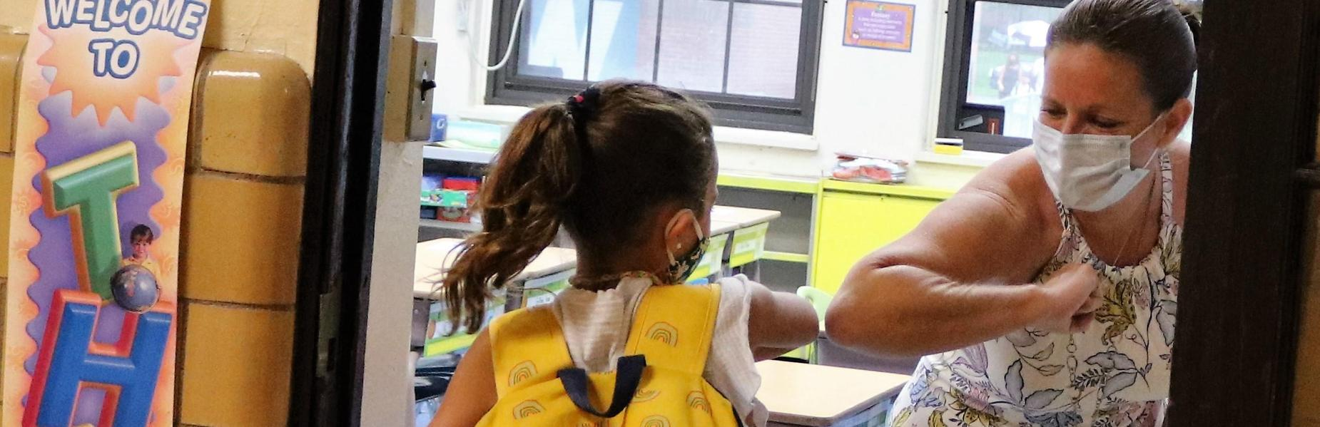 Photo of teacher and student elbow bumping on first day of school while wearing masks.