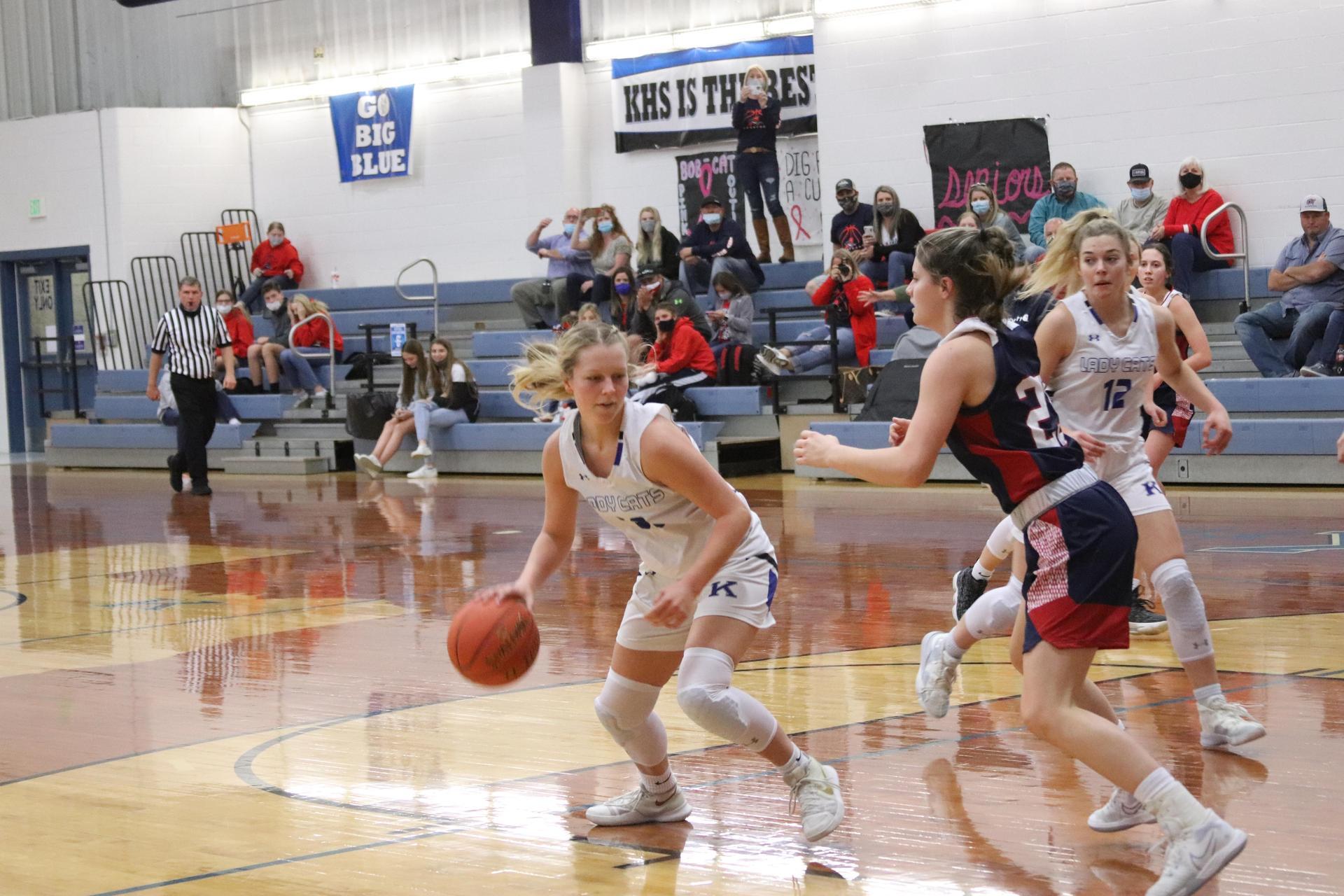 a female basketball player dodges around a guard
