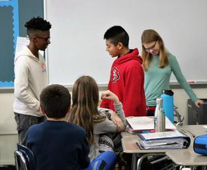 Photo of two 6th graders at Edison performing a scenario on effective communication as part of 8th grade peer leader session.