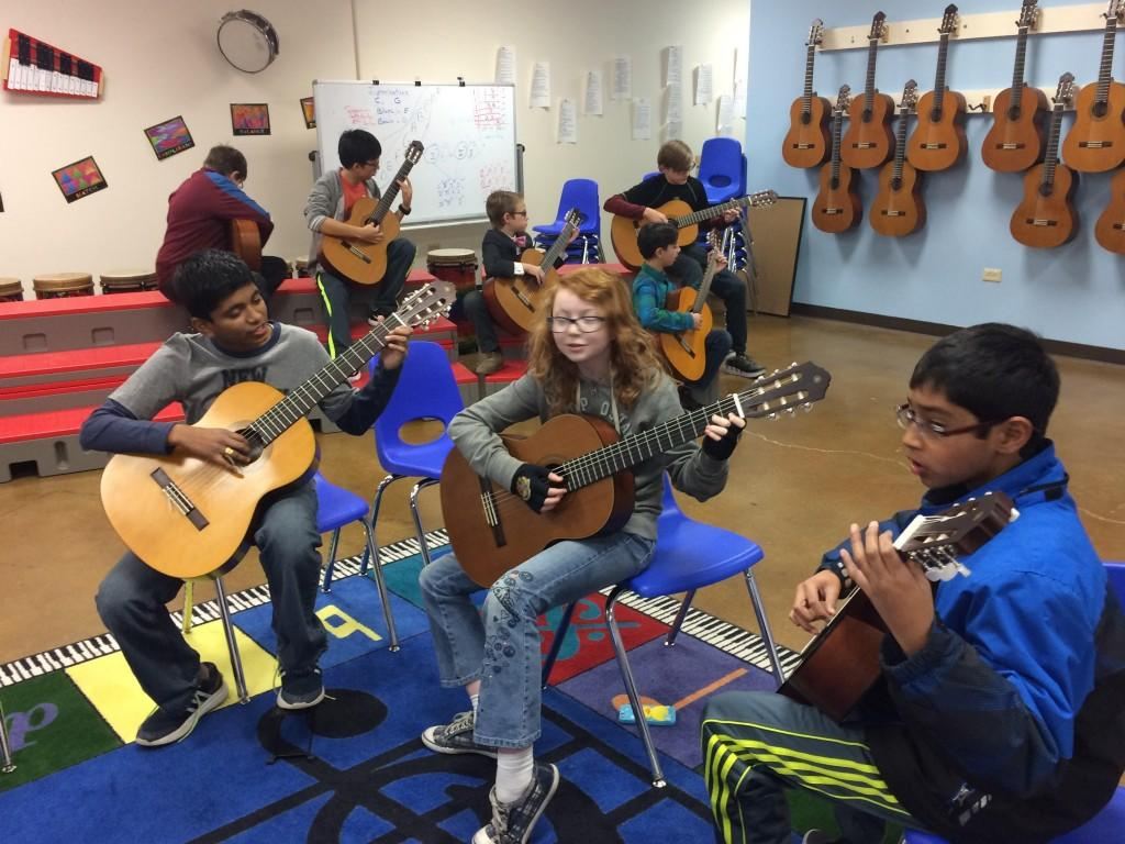 Middle school students learn guitar