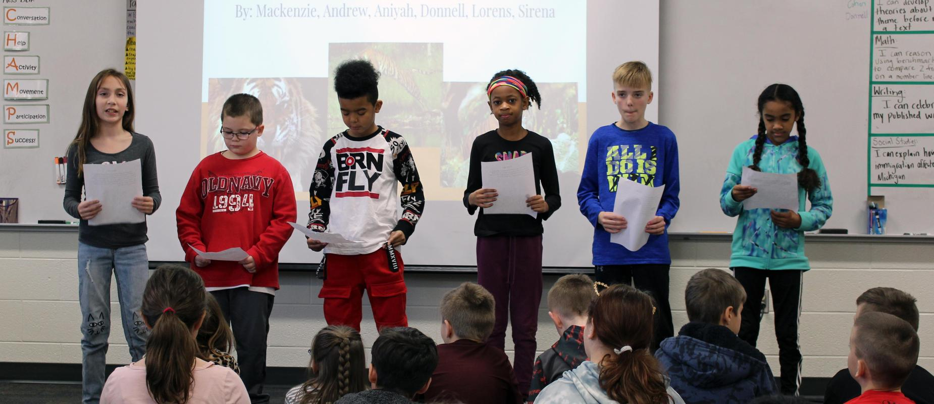 six fourth graders present their papers to the rest of the class in the front of the room