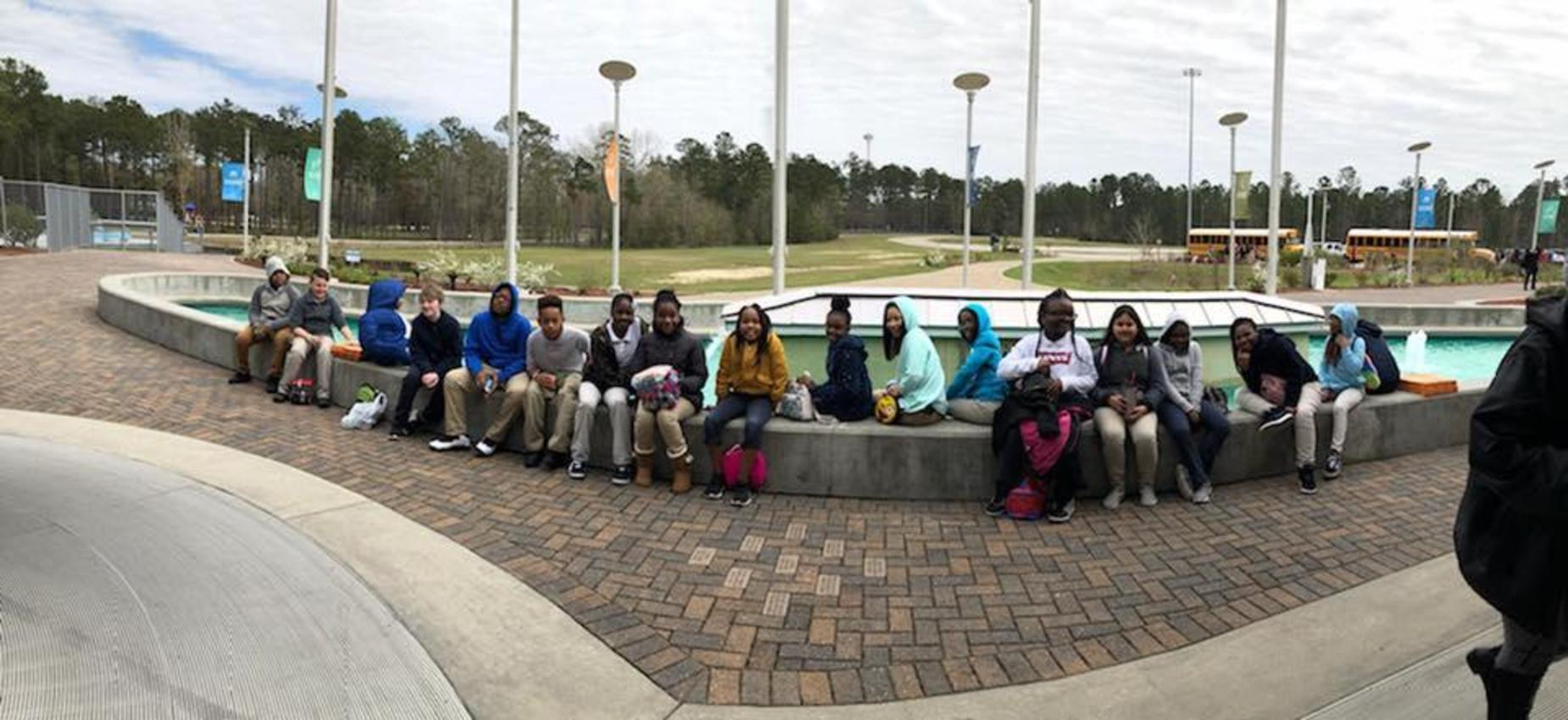 students sitting around fountain