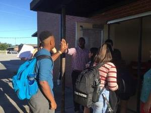 Students giving high fives entering school