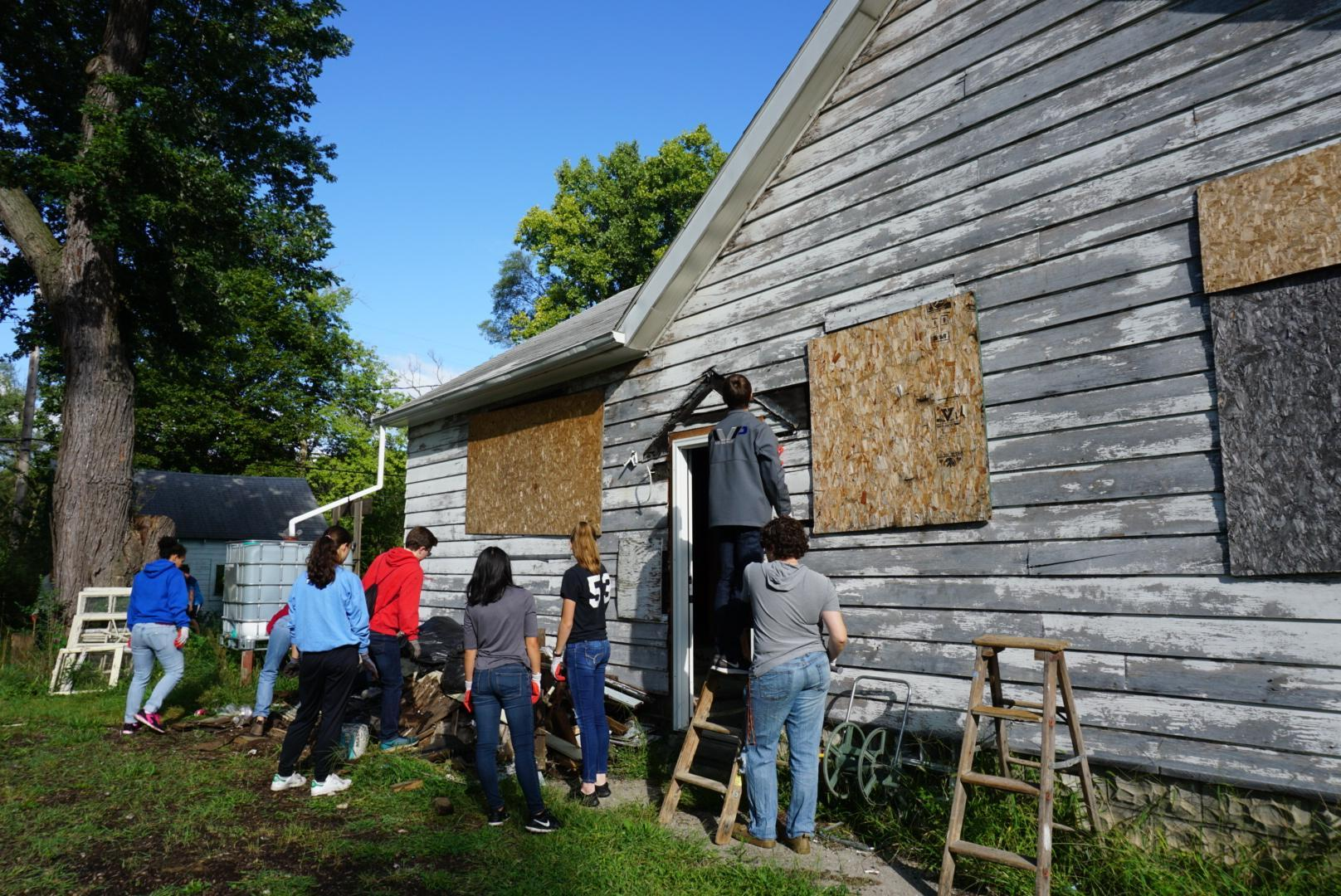 picture of students scraping old house on C day
