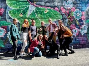 Students posing with mural