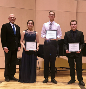 four people wearing black holding certificates