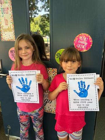 Students holding thank you bags for the police officers