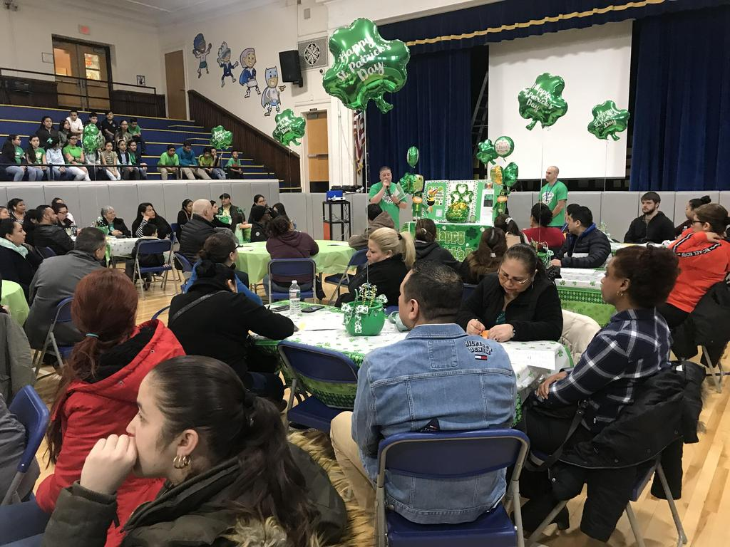 mr. Rivera addressing the parents in the gym who are sitting at table decorated for St. Patricks Day