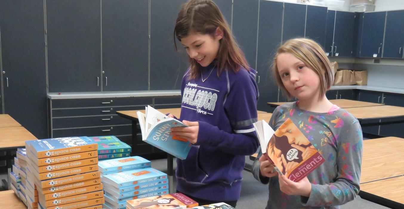 Page students look over books for the Battle of the Books competition.