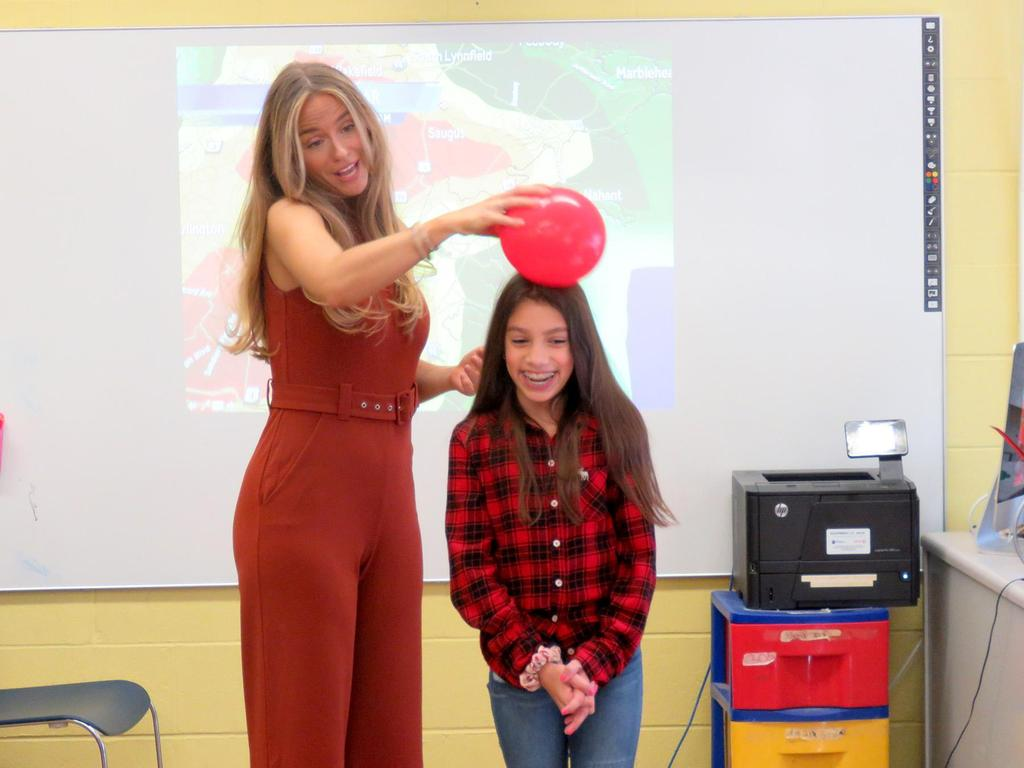 Using a balloon on the top of fifth grader Sophia Almeida's head, Kelly Ann Cicalese explains a meteorological concept