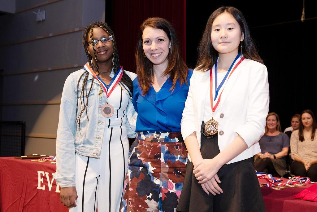 Teacher Katelyn Crossley presents medals to two seventh graders