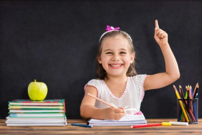 girl pointing up and smiling. back to school
