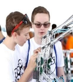 two boys in white shirts work on robots
