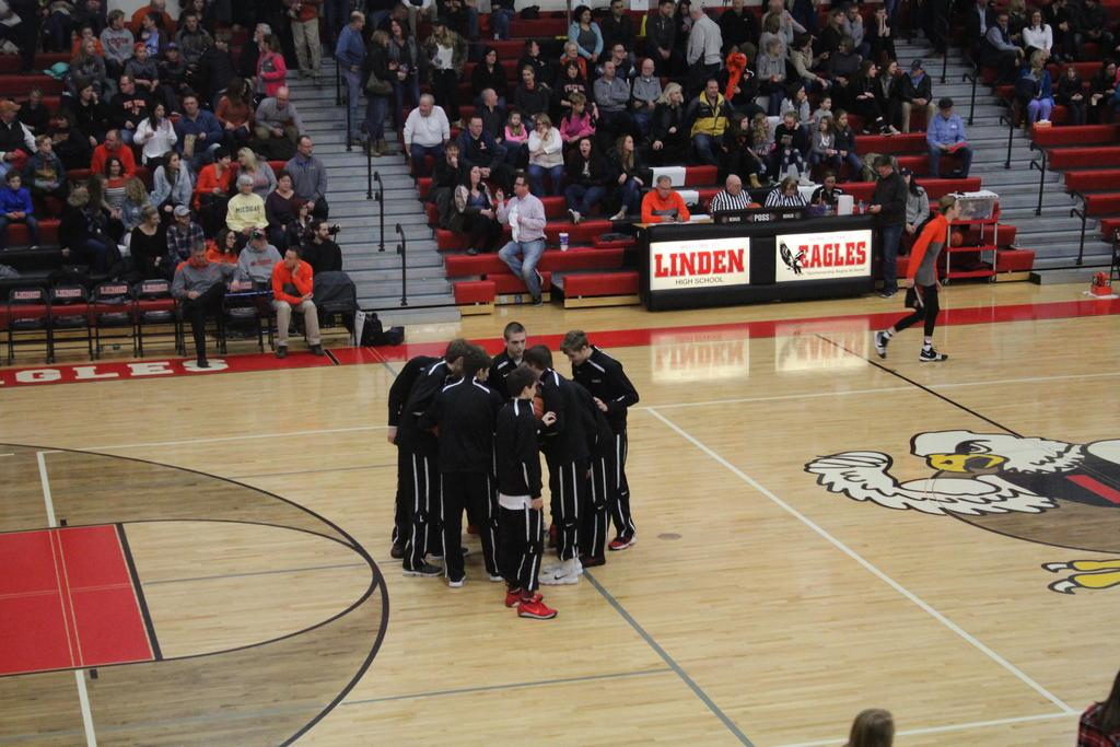 Group of basketball players in black warmups huddled together near the center of the gym floor.